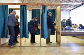 People vote at a polling station in Ogre, Latvia, during general elections, Oct. 6, 2018.