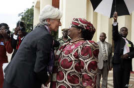 FILE - International Monetary Fund Managing Director Christine Lagarde is greeted by Malawi's President, Joyce Banda, on arrival at Kamuzu Palace in Lilongwe on her three day official visit to Malawi, Jan. 4, 2013.