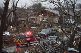 An emergency vehicle drives through a neighborhood in Rowlett, Texas, Dec. 27, 2015, the morning after it was struck by a tornado.