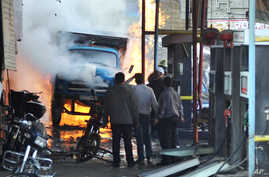 In this photo released by the Syrian official news agency SANA, Syrian citizens stand near a burning truck that was destroyed by two cars bombs in the Jermana neighborhood, a suburb of Damascus, Syria, November 28, 2012.