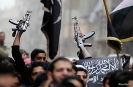 """A man with a weapon holds an Islamist flag during a protest against Syria's President Bashar al-Assad in Bustan al-Qasr district in Aleppo, March 22, 2013. The flag reads, """"There is no God but Allah and Mohammad is the messenger of Allah"""" REUTERS/Gia"""