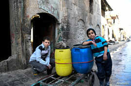 FILE - Boys are pictured beside a cart they use to carry water back to their home in the east Aleppo neighborhood of al-Mashatiyeh, Syria, in this handout picture provided by UNHCR, Jan. 4, 2017.