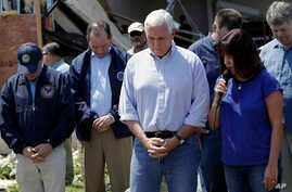 Vice President Mike Pence, center, and other bow their heads as his wife, Karen prays during a visit to the First Baptist Church of Rockport, Aug. 31, 2017, in Rockport, Texas. The church received heavy damage from Hurricane Harvey.