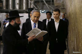 FILE - Israel's Prime Minister Benjamin Netanyahu, center, reads a prayer with Western Wall Rabbi Shmuel Rabinowitz, left, as his son Yair, right, stands next to him, at the Western Wall, Judaism's holiest prayer site, in Jerusalem's Old City, March