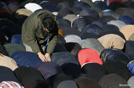 FILE - Muslim demonstrators pray during a protest in central London that followed publication of cartoons depicting the Prophet Muhammad in the French magazine Charlie Hebdo,  Feb. 8, 2015.