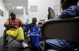 FILE - Ali Said, of Somalia, left, waits at a center for refugees with his two sons, July 6, 2017, in San Diego. Said, whose leg was blown off by a grenade, says he felt unbelievably lucky to be among the last refugees allowed into the United States