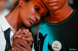 A boy comforts a crying girl during a special prayer for the passengers of the missing Malaysia Airlines flight MH370 in central Kuala Lumpur, March 18, 2014