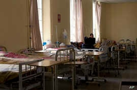 FILE - A patient sits among empty beds inside the General Hospital during a doctors' strike in La Paz, Bolivia, Dec. 11, 2017. Public sector doctors in Bolivia announced a 2-day strike Wednesday to protest universal health care.