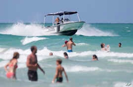 Members of Miami Beach Ocean Rescue keep an eye on swimmers due to the high risk of rip currents in the area Tuesday, July 19, 2016, on South Beach in Miami Beach, Florida.