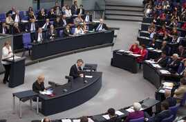 German Chancellor Angela Merkel, left, addresses lawmakers on the decisions of the EU summit at the parliament Bundestag in Berlin, June 29, 2012.