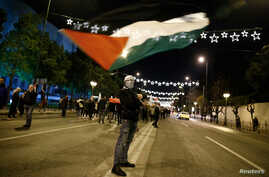 A demonstrator waves a Palestinian flag during a protest against Donald Trump's decision to recognize Jerusalem as the capital of Israel, in Athens, Greece, Dec. 8, 2017.