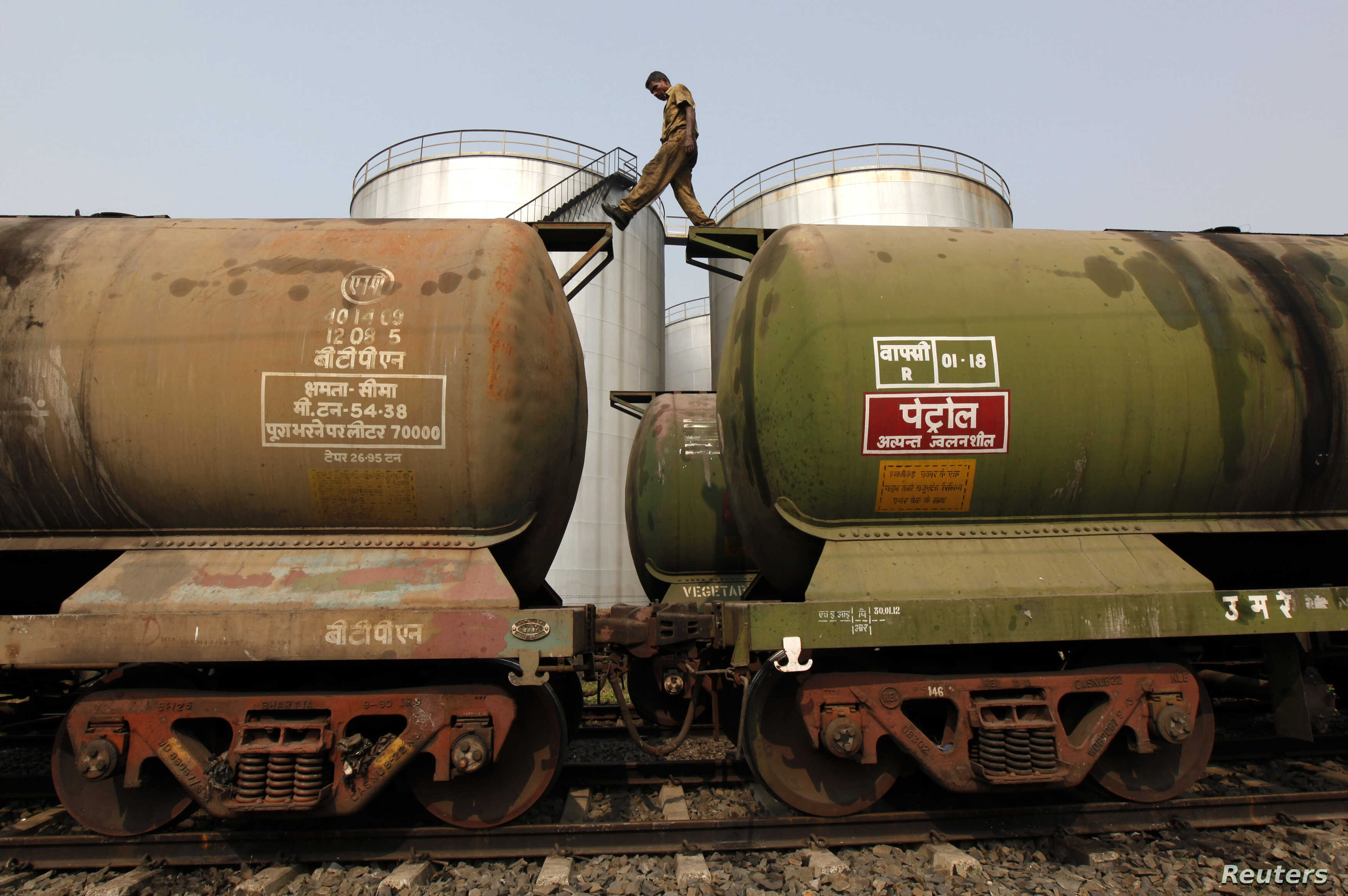 A worker walks atop a tanker wagon to check the freight level at an oil terminal on the outskirts of Kolkata, Nov. 27, 2013.