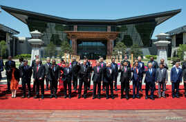 Leaders attending the Belt and Road Forum wave as they pose for a group photo at the Yanqi Lake venue on the outskirt of Beijing, China, May 15, 2017.