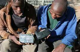 Two men in Bulawayo, Zimbabwe listen to a battery-operated radio for the results of the country's 2008 elections in this file photo.