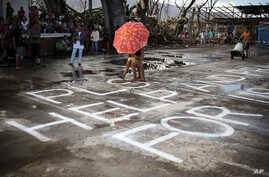 """Survivors of Typhoon Haiyan walk over a """"Help"""" message painted on a concrete floor, Saturday, Nov. 16, 2013 in Burauen town, Leyte province, central Philippines."""