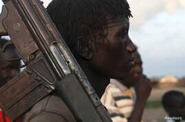 A man from the Luo Nuer tribe carries his gun in Yuai Uror county, South Sudan, July 24, 2013