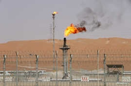 FILE - Flames are seen at the production facility of Saudi Aramco's Shaybah oilfield in the Empty Quarter, Saudi Arabia, May 22, 2018.
