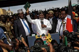 "FILE - Opposition leader Raila Odinga, center, accompanied by lawyers Miguna Miguna, center-left, Tom ""T.J."" Kajwang, center-right, and politician James Orengo, right, holds a Bible aloft after a mock ""swearing-in"" ceremony at Uhuru Park in downtown"