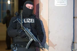 A German police officer stands outside a Berlin apartment building after a raid there against suspected jihadists, Jan. 16, 2014.
