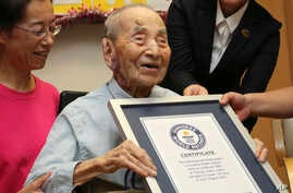 Yasutaro Koide, 112, receives the Guinness World Records certificate as he is formally recognized as the world's oldest man at a nursing home in Nagoya, central Japan, Aug. 21, 2015.