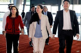 American couple Grace, center, and Matthew Huang, right, walk to their departure gate with U.S. Ambassador to Qatar, Dana Shell Smith, left, at the Hamad International Airport in Doha, Qatar, Dec. 3, 2014.