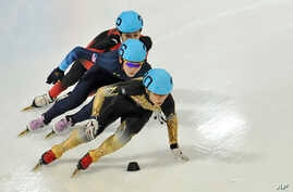 FILE - Japan's Kei Saito leads in front of Thomas Insuk Hong, of the United States, and China's Lu Xiucheng as they compete in the men's 1000 meter short track speed skating competition in Innsbruck, Austria.