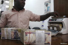 A money dealer counts the Nigerian naira on a machine in his office in the commercial capital of Lagos.