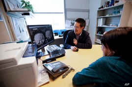 FILE - Patient Alison Cairnes (foreground) looks at images with her doctor Shumei Kato at the University of California San Diego in San Diego, Aug. 15, 2017.