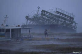 A person reacts to the weather as a ship washed ashore by Typhoon Trami is seen at a port in Yonabaru, on the southern island of Okinawa, Japan, Sept. 29, 2018.