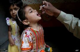A health worker gives a polio vaccine to a girl in Lahore, Pakistan, April 9, 2018. A Pakistani official said authorities launched a new polio vaccination drive, aiming to reach 38.7 million children younger than 5.