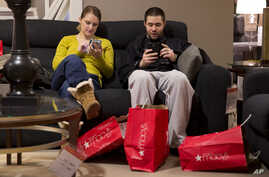 Andrea and Karl Galvez of Chicago take a break from shopping during Black Friday shopping at Macy's on Nov. 29, 2013, in Chicago.