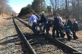 Emergency first responders and passengers from an Amtrak passenger train carrying Republican members of the U.S. Congress from Washington to a retreat in West Virginia carry one of the injured across train tracks to an ambulance after the train colli