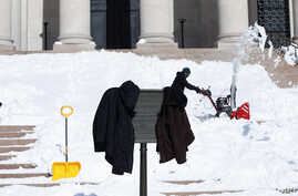 Workers jackets hang on a sign as they clear snow from the steps of the West Building of the National Gallery of Art in Washington, Jan. 25, 2016.