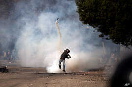 An Egyptian protester throws a tear gas canister back at riot police, not seen, during clashes near Tahrir Square, Cairo, Egypt, Sunday, Jan. 27, 2013.