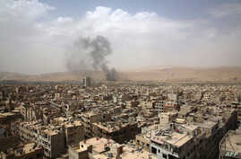 Picture shows smoke billowing from the Syrian rebel-held area of Douma, east of the capital Damascus, following a reported air strike by Syrian government forces, Sept. 14, 2015