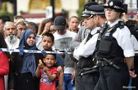 A young boy plays with a water pistol as onlookers stand at the police cordon as police search a property in Barking Road, east London, June 4, 2017.