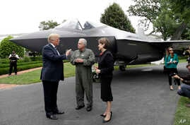 "President Donald Trump talks with Lockheed Martin president and CEO Marilyn Hewson and director and chief test pilot Alan Norman in front of a F-35 as he participates in a ""Made in America Product Showcase"" at the White House, July 23, 2018."