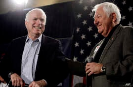 FILE - Sen. John McCain, R-Ariz., left, smiles as he gets a pat on the back from longtime friend and supporter Lt. Col. Orson Swindle, USMC Ret., Feb. 18, 2010, in Phoenix. McCain was in a primary election battle with former Republican congressman J.