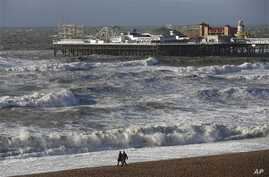 People walks along the shoreline as waves crash onto the beach in Brighton, England, Monday, Oct. 28, 2013.  A major storm with hurricane force winds is lashing much of Britain, causing flooding and travel delays with the cancellation of many flights