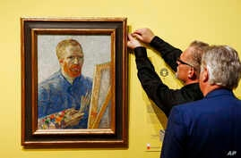 FILE - Curators hang the 1888 self-portrait of Vincent Van Gogh in Amsterdam, The  Netherlands, May 1, 2013.