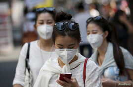 A tourist wearing a mask to prevent contracting Middle East Respiratory Syndrome (MERS) uses her mobile phone at Myeongdong shopping district in central Seoul, South Korea, June 10, 2015.