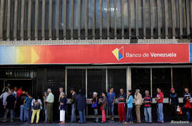 People line up to withdraw cash from a Banco de Venezuela branch in Caracas, Venezuela, Dec. 2, 2016. Venezuela's struggling economy took another hit on Friday when it's association with Mercosur was suspended.