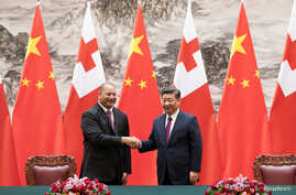 FILE - King Tupou VI, left, of Tonga shakes hands with Chinese President Xi Jinping at The Great Hall of the People, in Beijing, March 1, 2018.