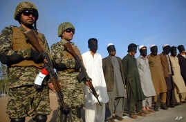 Pakistani paramilitary soldier stand guard next to suspects arrested during a search operation in Shah Kass, an area of Pakistani Khyber tribal region along Afghan border, March 3, 2017.