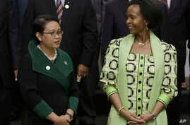 Indonesian Foreign Minister Retno Marsudi, left, talks with her South African counterpart Maite Nkoana-Mashabane as they prepare for a group photo prior to the opening session of the Asian African Ministerial Meeting in Jakarta, Indonesia, April 20,