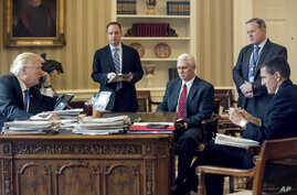 President Donald Trump accompanied by, from second from left, Chief of Staff Reince Priebus, Vice President Mike Pence, White House press secretary Sean Spicer and National Security Adviser Michael Flynn speaks on the phone with Russian President Vla