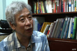 FILE - Former professor Sun Wenguang speaks in his home in Jinan, east China's Shandong province, Aug. 28, 2013.
