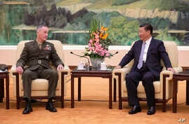 U.S. Chairman of the Joint Chiefs of Staff Gen. Joseph Dunford, left, chats with President Xi Jinping during a meeting at the Great Hall of the People in Beijing, Aug. 17, 2017.