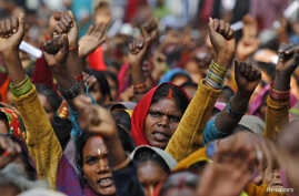 FILE - Forest dwellers raise their hands and shout slogans during a rally in New Delhi, India, Dec. 15, 2011.
