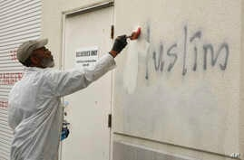 "A man paints over racist graffiti, which included such pronouncements as ""Muslims out,"" on the side of a mosque in what officials are calling an apparent hate crime, in Roseville, California, Feb. 1, 2017."